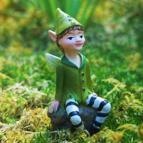 boy fairy figurine sitting on stone