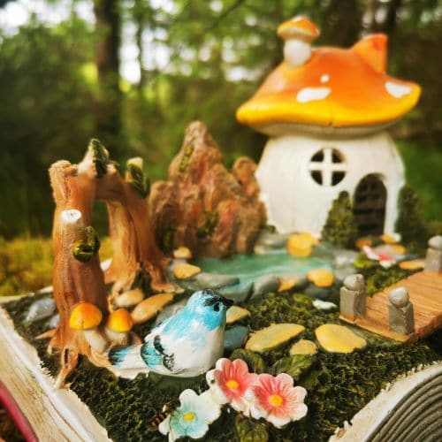 fairy tale house with bird and pond